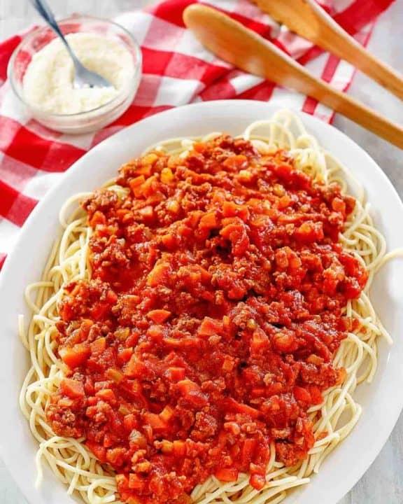homemade Olive Garden Beef Bolognese over pasta on a platter