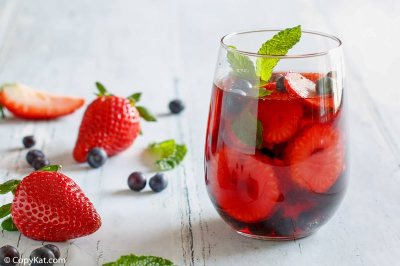 a glass of berry sangria, strawberries, blueberries, and mint leaves