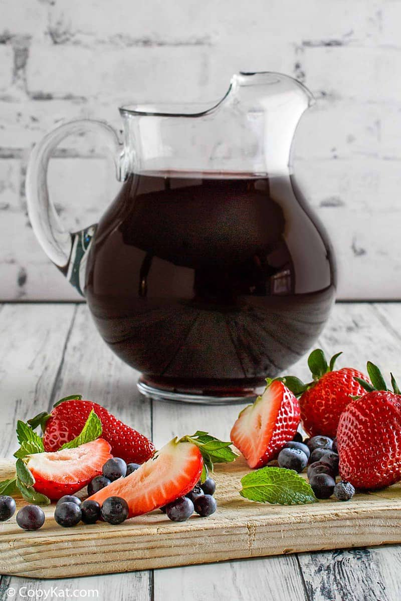 a pitcher of homemade Olive Garden Berry Sangria, strawberries, and blueberries