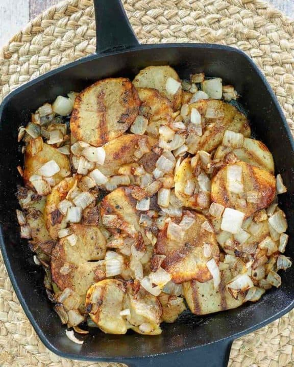 cooked sliced potatoes and onions in a skillet