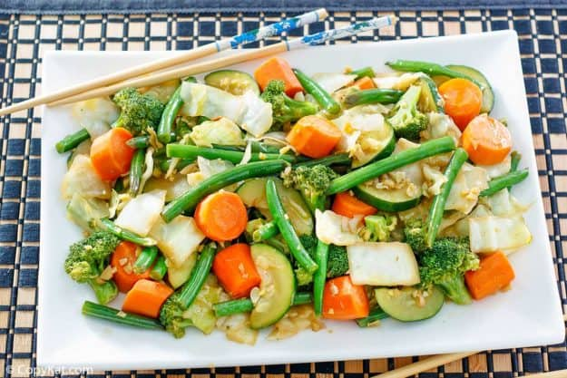 cooked broccoli, cabbage, carrots, green beans, and zucchini on a platter