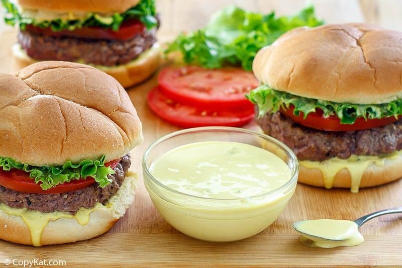 a bowl of homemade Smashburger Smash Sauce and three burgers