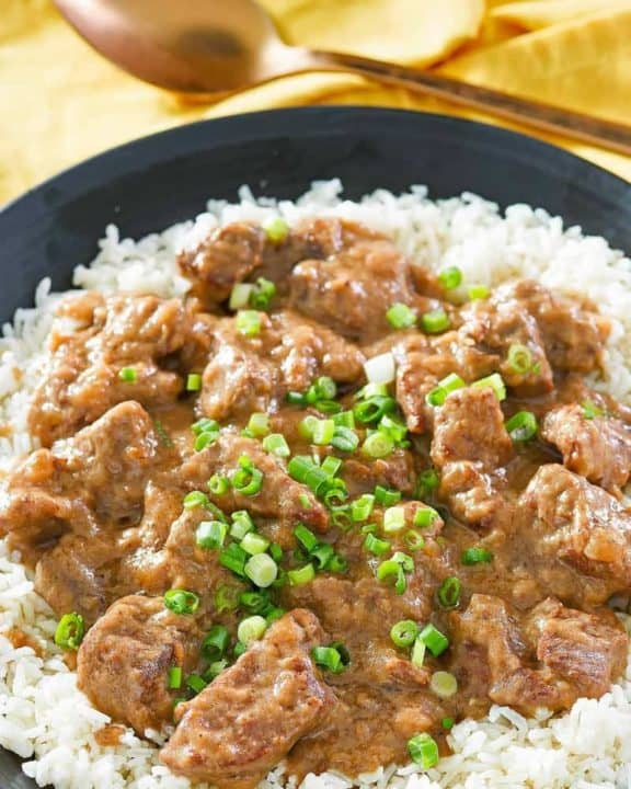 beef tips and gravy over rice on a black plate