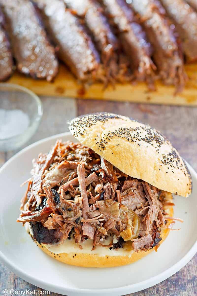 a brisket sandwich in front of brisket slices