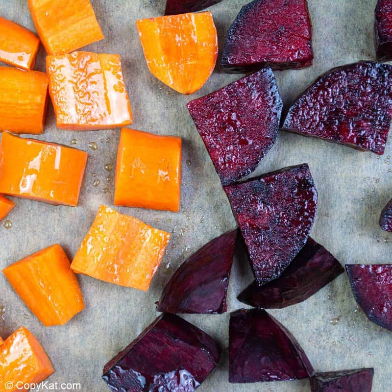 chopped carrot and red beet on a baking sheet