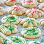 cream cheese spritz cookies scattered on parchment paper