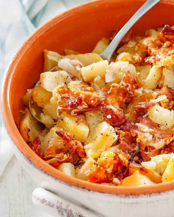 Crockpot cheesy potatoes with bacon and a spoon in a bowl