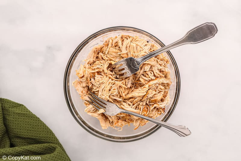 shredded chicken and two forks in a bowl