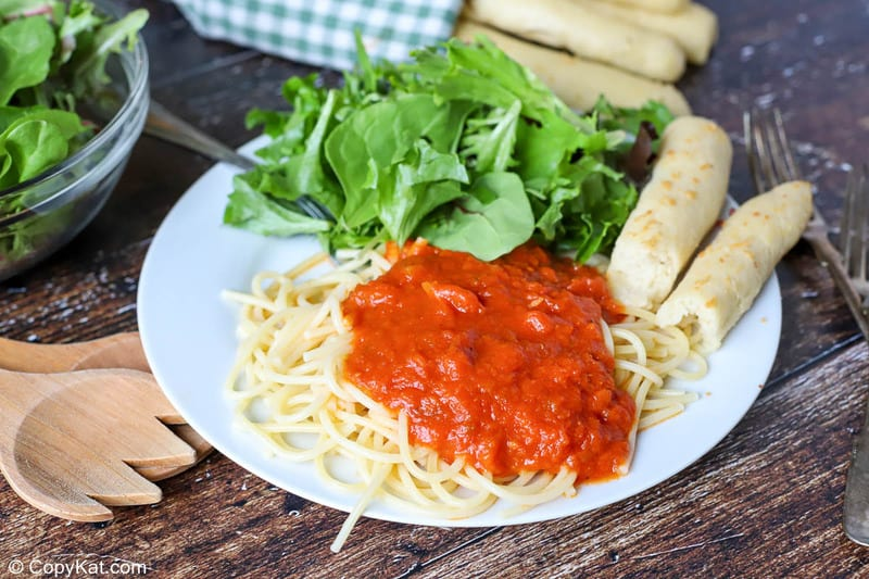 Homemade Olive Garden breadsticks, pasta with marinara, and salad on a plate