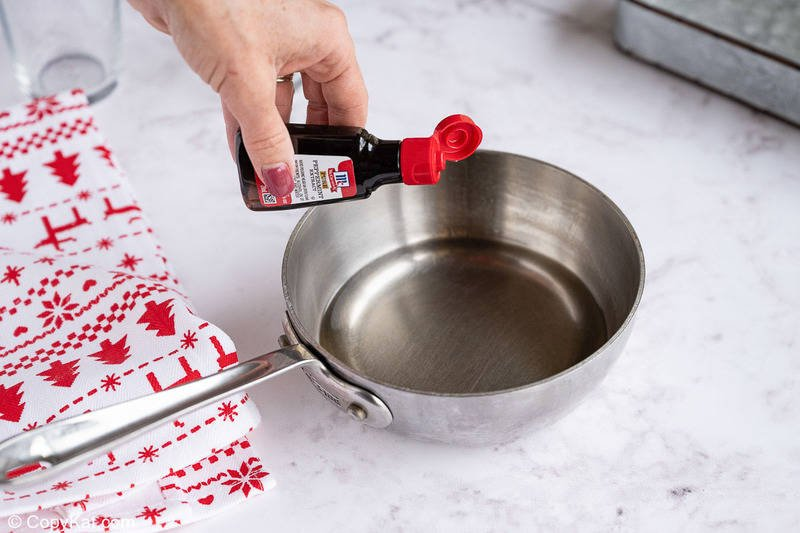 adding peppermint extract to simple syrup in a pan