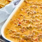 Rotel dip with ground beef in a dish next to a basket of tortilla chips