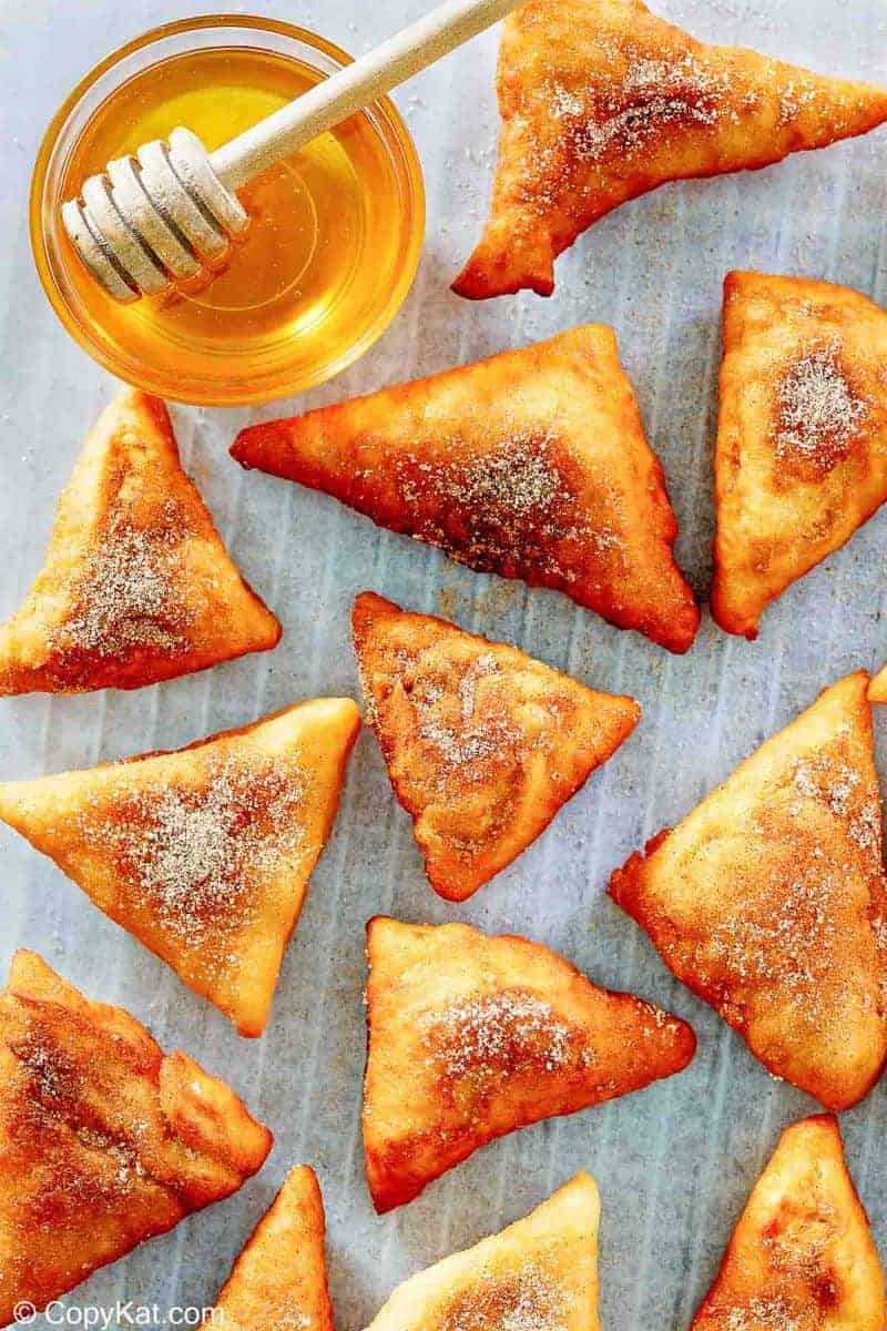 sopapillas and honey on parchment paper