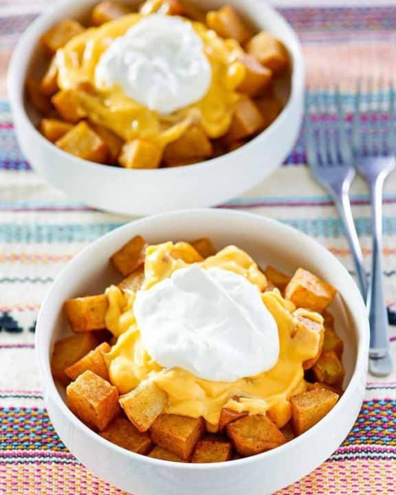 two bowls of homemade Taco Bell Cheesy Fiesta Potatoes bowls