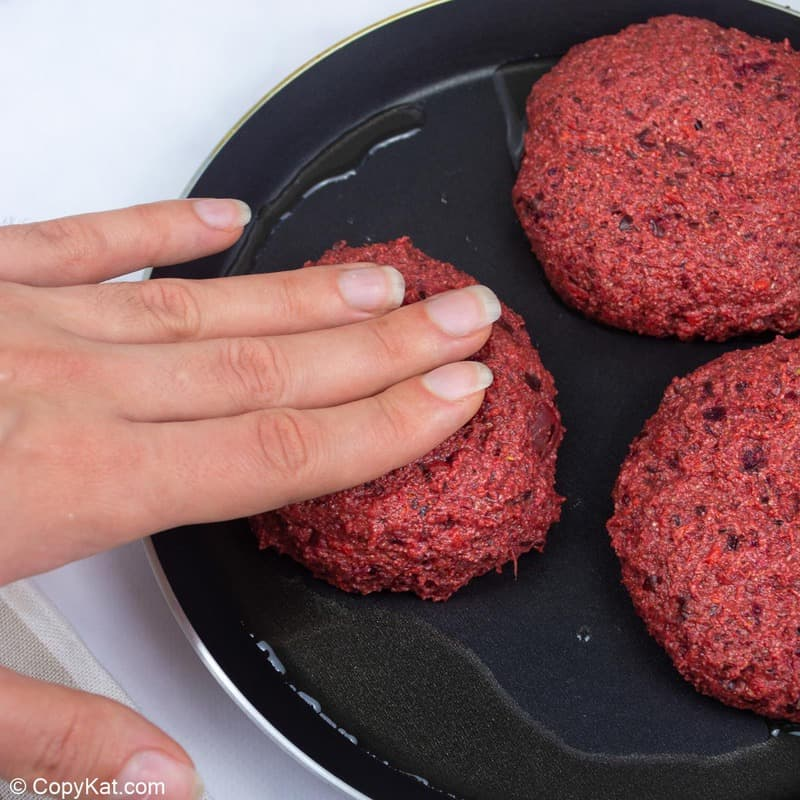three vegan burger patties in a skillet
