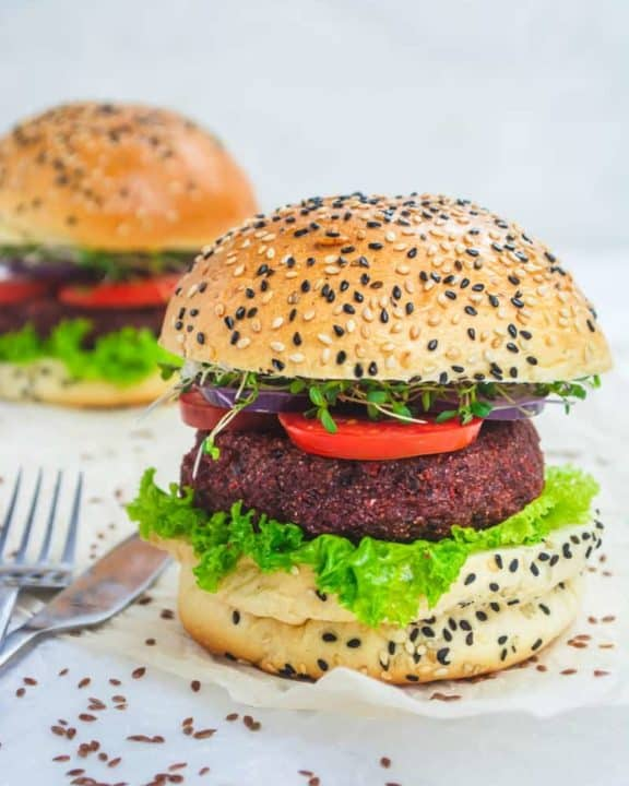 two vegan burgers with lettuce and tomato on sesame seed buns