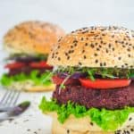 two vegan burgers with lettuce, tomato, onion, sprouts, and sesame seed buns