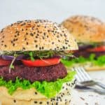 two vegan burgers with lettuce, tomato, and sesame seed buns