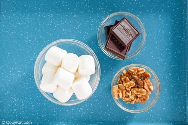 large marshmallows, chocolate pieces, and chopped walnuts in bowls