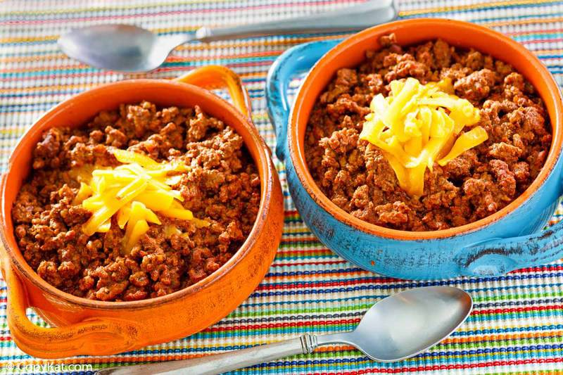 bowls of homemade Wick Fowler 2 Alarm Chili with shredded cheese on top