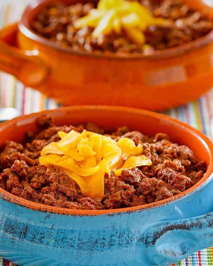 bowls of homemade Wick Fowler 2 Alarm Chili topped with cheese