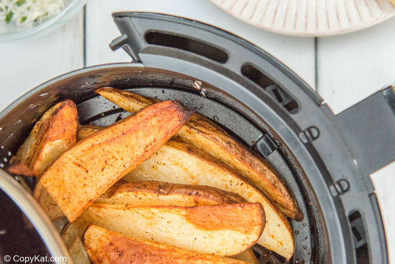 cooked potato wedges in an air fryer basket