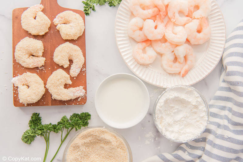 panko breaded shrimp on a wood board, raw shrimp, and breading ingredients in bowls