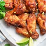 overhead view of air fryer sweet and spicy chicken wings and lime wedges on a platter