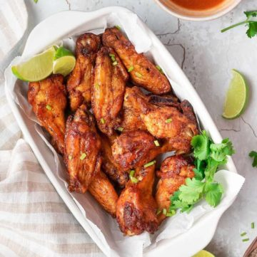 overhead view of air fryer sweet and spicy chicken wings in a dish and bowls of sauce and dressing