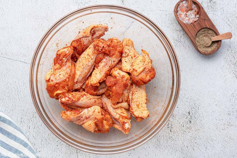sweet and spicy seasoned raw chicken wings in a mixing bowl