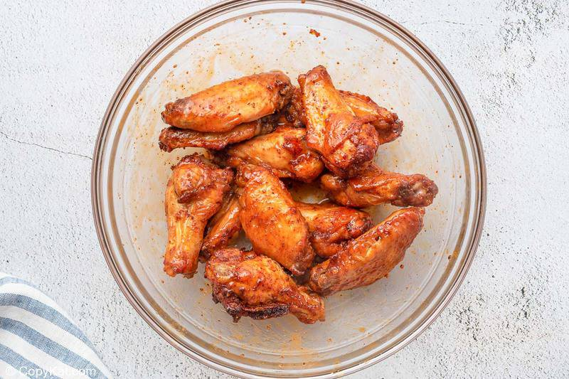 sweet and spicy chicken wings tossed with sauce in a bowl