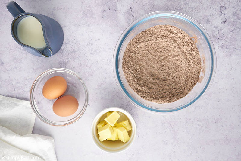 flour and cocoa powder mixture in a bowl, milk, eggs, and butter