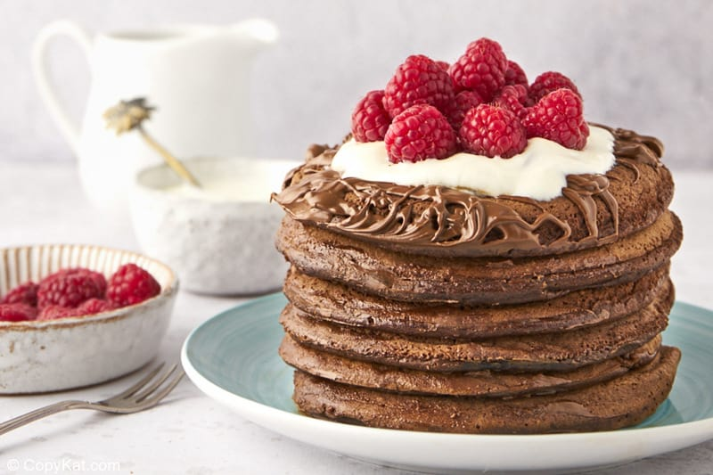 a stack of six chocolate pancakes, raspberries, cream, and a small pitcher