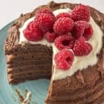 chocolate pancakes topped with raspberries and whipped cream with a wedge cut out of the stack