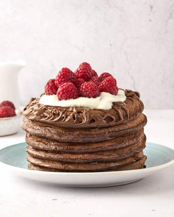 a stack of six chocolate pancakes topped with chocolate spread, whipped cream, and raspberries