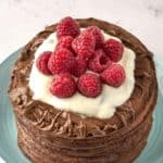 a stack of chocolate pancakes topped with chocolate spread, whipped cream, and raspberries