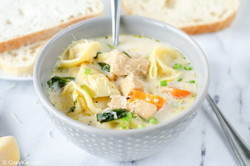 a bowl of creamy chicken tortellini soup and slices of bread