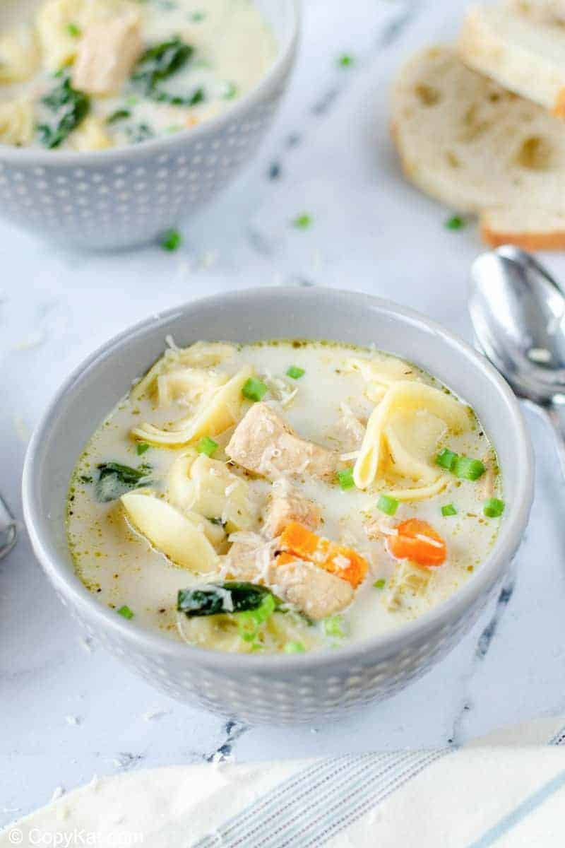 two bowls of creamy chicken tortellini soup and bread slices