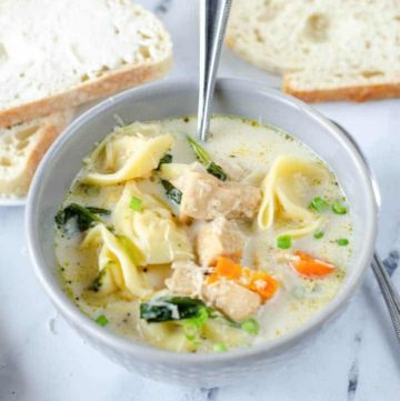 creamy chicken tortellini soup in a bowl and bread slices