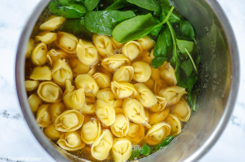 broth, tortellini, and spinach in an Instant Pot bowl