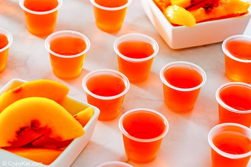 peach jello shots and two dishes of peach slices