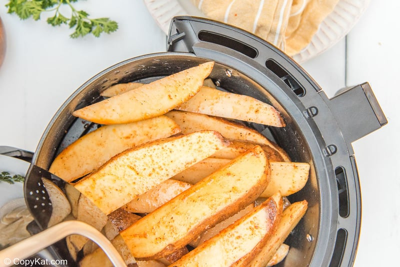 seasoned potato wedges in an air fryer basket before cooking