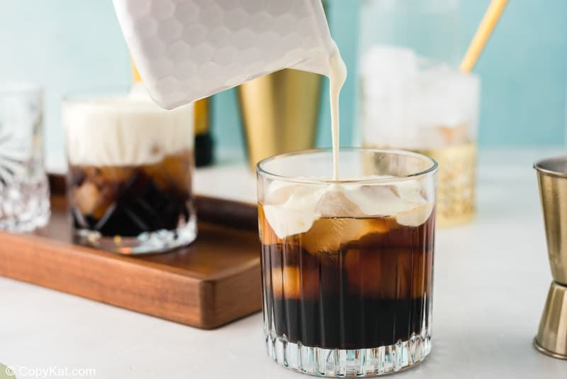 pouring cream over Kahlua, vodka, and ice in a glas