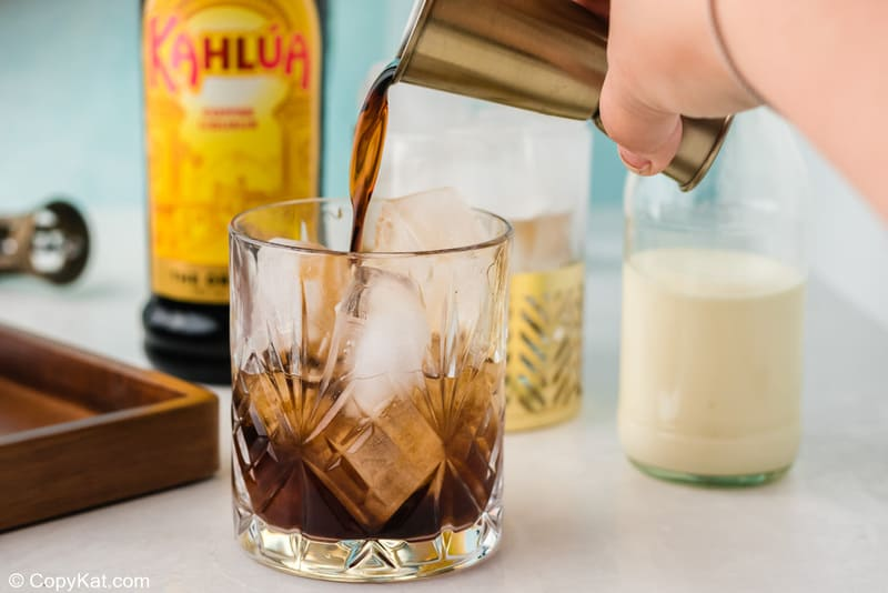 pouring Kahlua over vodka and ice in a glass