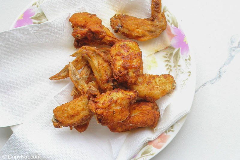 fried spicy chicken wings on paper towels