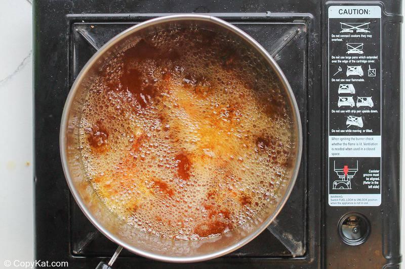spicy chicken wings deep frying in a pan