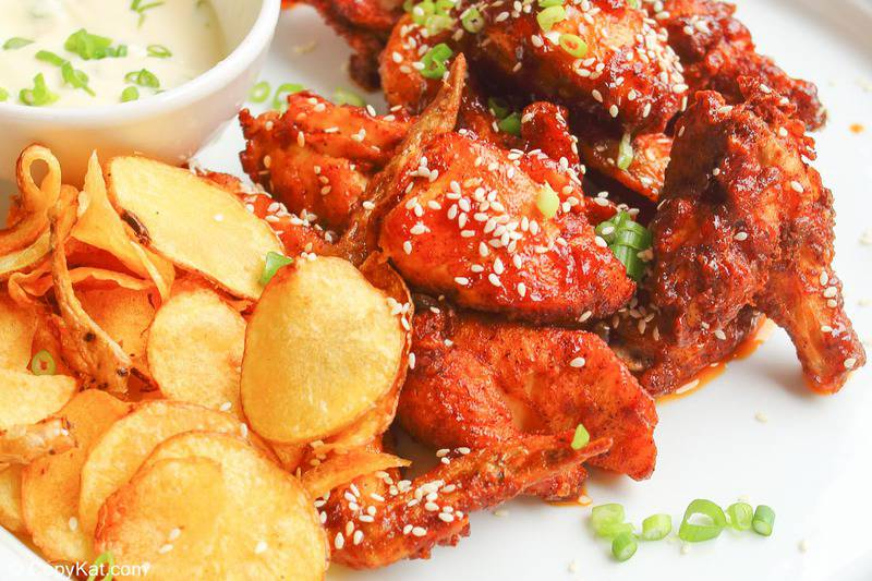 potato chips, dipping sauce, and spicy chicken wings on a plate