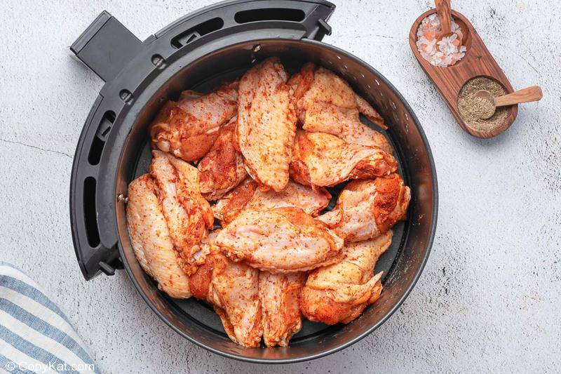 sweet and spicy seasoned chicken wings in an air fryer basket