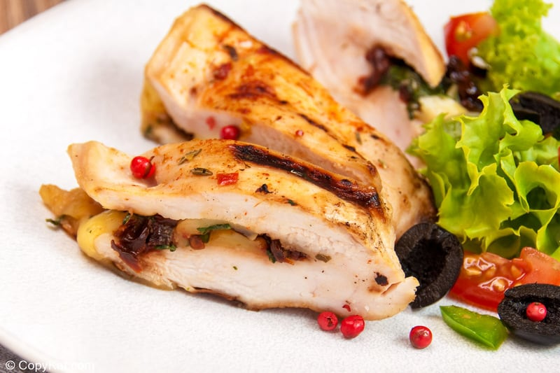 chicken breast stuffed with blue cheese, black olives, basil, and sun-dried tomatoes on a plate