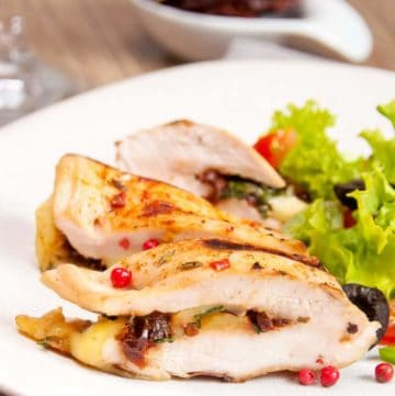 blue cheese and black olive stuffed chicken breast on a plate with a salad