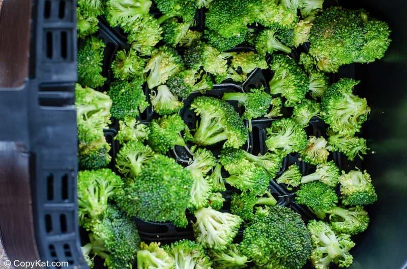 seasoned broccoli in an air fryer basket